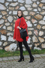 Pretty girl in red handmade knitted poncho with fries. Standing position in park