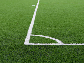 White lines on soccer field corner, artificial grass texture.