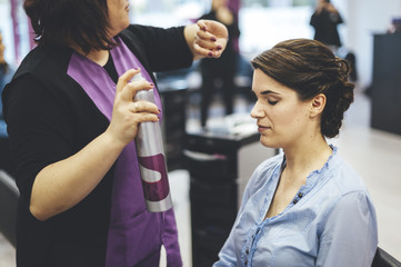 Hairdresser applying hair spray to a bride