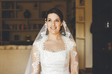 Portrait of a smiling bride getting dressed with veil