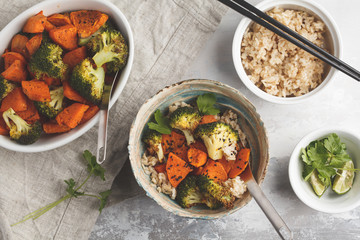 Brown rice with baked broccoli and sweet potato on white background, top view. Healthy vegan food concept.