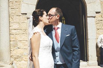Bride and groom kissing at church door