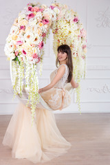 A beautiful bride in a wedding dress in an interior sits on a hanging circle in floral arrangements