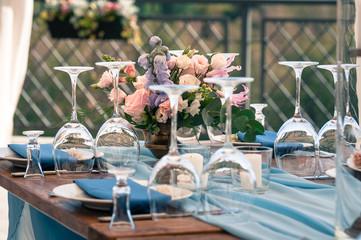 Wedding or Event decoration table setup, blue napkins, flowers, outdoors