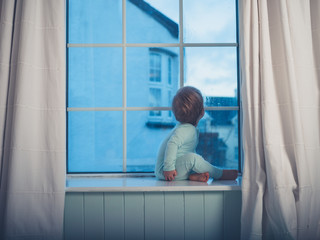 Little boy on window sill in the morning