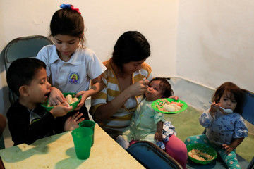 The children of Viviana Colmenares have lunch in a community diner at the slum of Petare in Caracas,