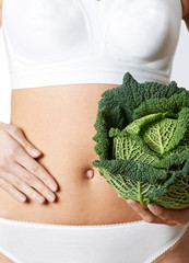 Close Up Of Woman In Underwear Holding Cabbage And Touching Stomach