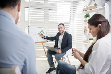 Developing business. Handsome joyful dark-haired man sitting in the chair and presenting his new ideas to his colleagues sitting and listening to him