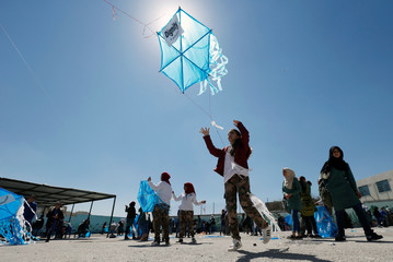 Schoolchildren prepare to fly kites at a United Nations-run school in Amman