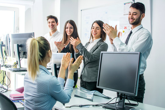 Smiling business group clapping hands at the meeting