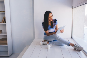 Surfing the internet . Pretty young latin woman using digital tablet while sitting at home near window