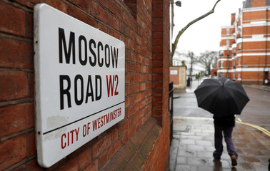 A person walks past the sign of Moscow road near to the Russian embassy in London