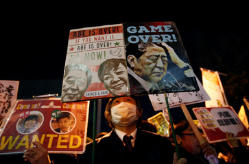 A protester holds placards denouncing Japanese Prime Minister Shinzo Abe at a rally in Tokyo
