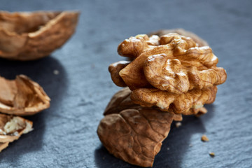 Top view close-up shot of cracked walnuts on dark background, shallow depth of field, macro