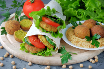 Falafel and vegetables wrapped in lavash and bowl with hummus on cutting board. Traditional arabic food. Close-up view.