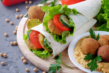 Falafel and vegetables wrapped in lavash and bowl with hummus on  light cutting board. Close-up view.