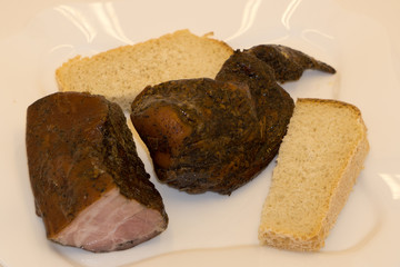 grilled pork meat on a white plate, a shish kebab from pork on a black background,next to the bread .