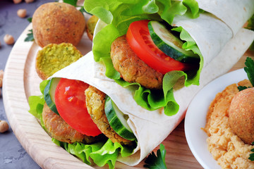 Falafel and vegetables wrapped in lavash on a light cutting board. Vegetarian and vegan food. Close-up view.