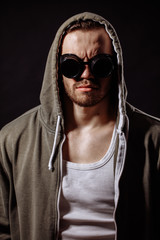 vertical portrait of angry young man wearing green hoodie and glasses. powerful evil.