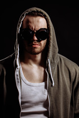 close up photo of unshaven man wearing glasses with thrown face on the black background