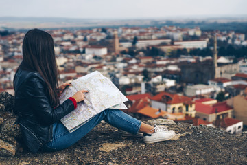 Young girl standing in front of beautiful city view and looking at the map.Panoramic view