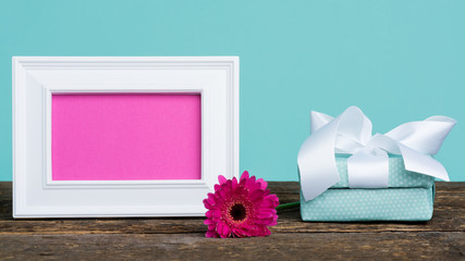 Happy Mother's Day, Women's Day, Valentine's Day or Birthday Pastel Candy Blue Coloured Background. Dark pink gerbera on a table with empty picture frame and a present.
