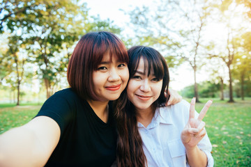 Two beautiful happy young asian women friends having fun together at park and taking a selfie. Happy hipster young asian girls smiling and looking at camera. Lifestyle and friendship concepts.