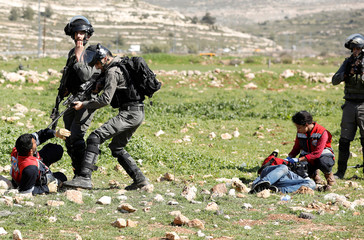 An Israeli border policeman points his weapon at a Palestinian medic during clashes near the Jewish settlement of Beit El, near Ramallah, in the occupied West Bank