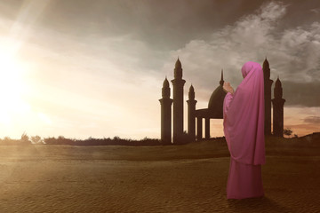 Rear view of asian muslim woman with veil pray to god