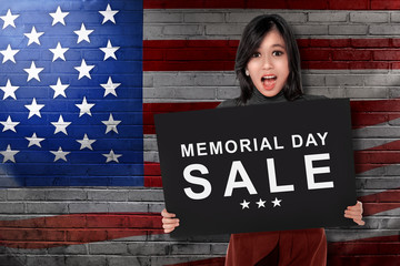 Young asian woman holding board with text memorial day sale