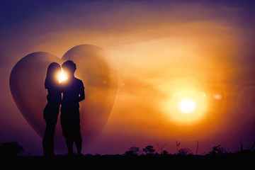The silhouette of romantic couple lovers stands hugging at sunset. The fantasy and love concept. Having a big heart shape around there.