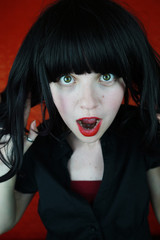 Mujer joven y expresiva fotografiada sobre fondo rojo