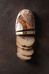 Loaf of fresh baked artisan sliced rye bread over dark brown texture background. Top view, copy space.