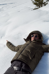 Young man in a warm hooded jacket and sunglasses lying on his back stretched out in the white winter snow with his arms outstretched
