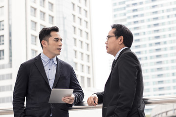 Businessman presenting work to boss, leader about planning project by laptop outside building.