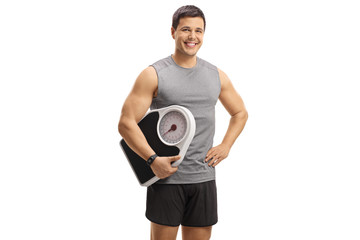 Young man in sportswear holding a weight scale