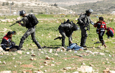 An Israeli border policeman detains a Palestinian protester as others hold back medics during clashes near the Jewish settlement of Beit El, near Ramallah