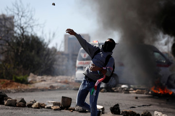 Palestinian protester hurl stones at Israeli troops during clashes near the Jewish settlement of Beit El, near Ramallah