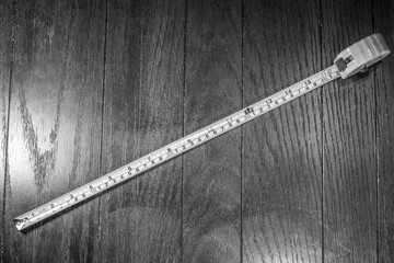 Black and White Tape Measurer on Wooden Background