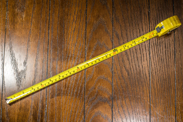 Yellow Tape Measurer on Wooden Background