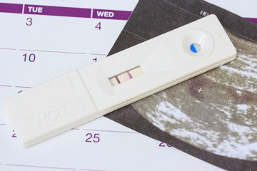 Pregnancy test on calendar background.