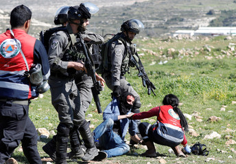 Israeli border policemen detain a wounded Palestinian protester during clashes near the Jewish settlement of Beit El, near Ramallah, in the occupied West Bank