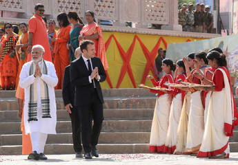French President Emmanuel Macron and Indian Prime Minister Narendra Modi walk together in Varanasi