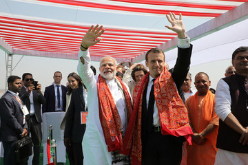 Indian Prime Minister Narendra Modi and French President Emmanuel Macron wave during the inauguration of a solar power plant in Mirzapur, in the northern Indian state of Uttar Pradesh