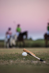 Polo Ball and Stick with Horse and Rider in Background at Sunset