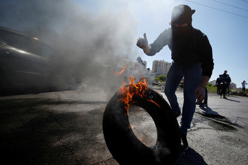 A Palestinian protester moves a burning tyre, during clashes with Israeli troops near the Jewish settlement of Beit El, near Ramallah, in the occupied West Ban