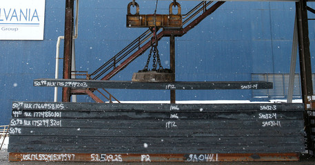 A overhead crane places a steel slab for storage at the Novolipetsk Steel PAO steel mill in Farrell, Pennsylvania