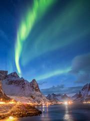 aurora borealis over norwegian snow covered mountains and illuminated road
