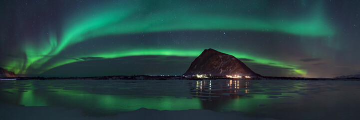 panorama view of northern lights / aurora borealis on dark sky over mountain in arctic norway, reflection on frozen lake