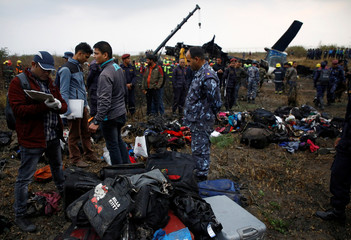 Officials check the belongings recovered from the cash site of a US-Bangla airplane at Tribhuvan International Airport in Kathmandu